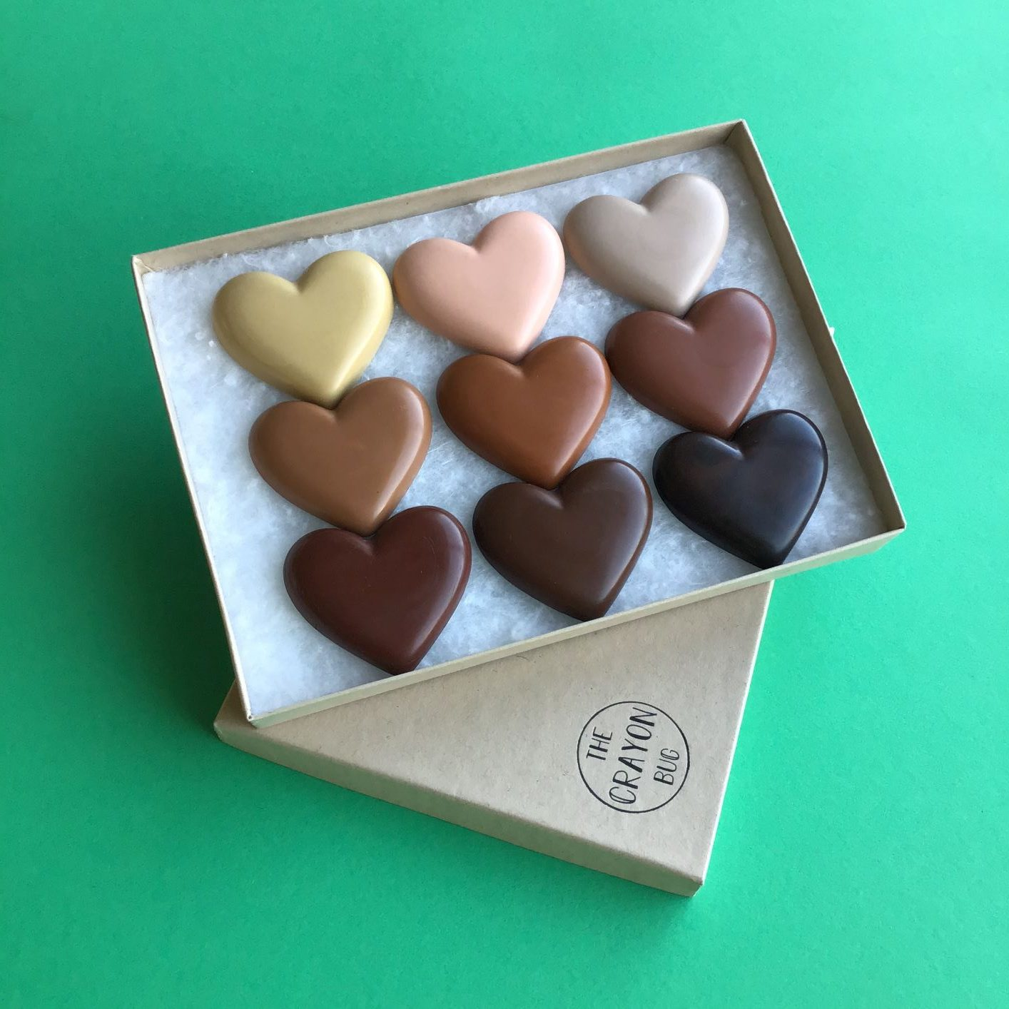 A box of handmade crayons in the shape of chocolates made by The Crayon Bug company