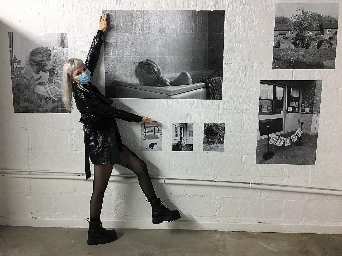 Josephine standing beside her photograph in an exhibition of the zine photos