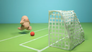 Stop motion clay figure kicking a football at a goal